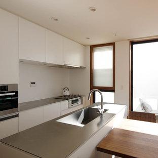 東京23区の広いモダンスタイルのおしゃれなキッチン (アンダーカウンターシンク、フラットパネル扉のキャビネット、白いキャビネット、ステンレスカウンター、白いキッチンパネル、セラミックタイルのキッチンパネル、黒い調理設備、濃色無垢フローリング、茶色い床、グレーのキッチンカウンター) の写真