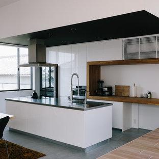 他の地域のアジアンスタイルのおしゃれなアイランドキッチン (シングルシンク、フラットパネル扉のキャビネット、白いキャビネット、グレーの床) の写真