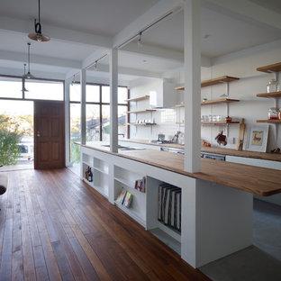 東京都下のアジアンスタイルのおしゃれなキッチン (シングルシンク、木材カウンター、白いキッチンパネル、セメントタイルのキッチンパネル、コンクリートの床、グレーの床、白いキッチンカウンター) の写真