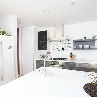 東京23区のモダンスタイルのおしゃれなキッチン (シングルシンク、フラットパネル扉のキャビネット、グレーのキャビネット、白いキッチンパネル、無垢フローリング、茶色い床) の写真