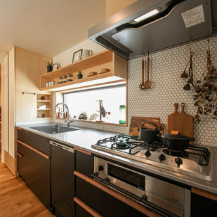 他の地域の北欧スタイルのおしゃれなキッチン (フラットパネル扉のキャビネット、黒いキャビネット、ステンレスカウンター、白いキッチンパネル、モザイクタイルのキッチンパネル、シルバーの調理設備、無垢フローリング、アイランドなし、茶色い床、一体型シンク) の写真