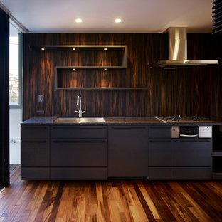 他の地域のコンテンポラリースタイルのおしゃれなI型キッチン (アンダーカウンターシンク、フラットパネル扉のキャビネット、黒いキャビネット、茶色いキッチンパネル、シルバーの調理設備の、濃色無垢フローリング、アイランドなし) の写真