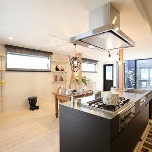 他の地域のアジアンスタイルのおしゃれなキッチン (一体型シンク、ステンレスカウンター、フラットパネル扉のキャビネット、黒いキャビネット、塗装フローリング、ベージュの床) の写真