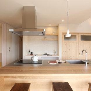 他の地域, のシャビーシック調のおしゃれなアイランドキッチン (一体型シンク、ステンレスカウンター、茶色いキッチンカウンター) の写真