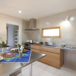 他の地域の北欧スタイルのおしゃれなキッチン (一体型シンク、ベージュのキャビネット、ステンレスカウンター、ベージュキッチンパネル、木材のキッチンパネル、淡色無垢フローリング、グレーの床) の写真