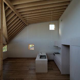 Immagine di una cucina ad U di medie dimensioni con lavello sottopiano, ante a filo, ante beige, top in superficie solida, paraspruzzi bianco, paraspruzzi in legno, elettrodomestici neri, pavimento in compensato, isola, pavimento marrone e top bianco