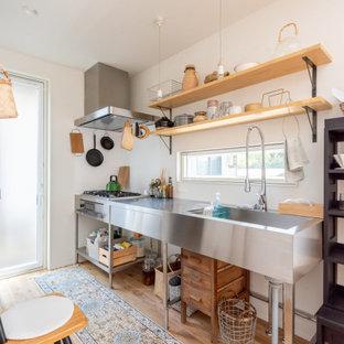 他の地域のインダストリアルスタイルのおしゃれなキッチン (一体型シンク、ステンレスカウンター、シルバーの調理設備、無垢フローリング、アイランドなし、茶色い床、グレーのキッチンカウンター) の写真
