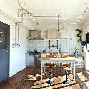 東京23区の小さいインダストリアルスタイルのおしゃれなキッチン (フラットパネル扉のキャビネット、ステンレスキャビネット、ソープストーンカウンター、白いキッチンパネル、サブウェイタイルのキッチンパネル、シルバーの調理設備の、無垢フローリング、アイランドなし、茶色い床) の写真