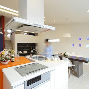 Große Moderne Wohnküche in L-Form mit Unterbauwaschbecken, gebeiztem Holzboden, zwei Kücheninseln, weißem Boden und oranger Arbeitsplatte in Sonstige
