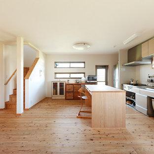 Offene, Einzeilige Asiatische Küche mit Waschbecken, flächenbündigen Schrankfronten, braunen Schränken, Edelstahl-Arbeitsplatte, Küchenrückwand in Weiß, braunem Holzboden, Kücheninsel, braunem Boden und brauner Arbeitsplatte in Sonstige
