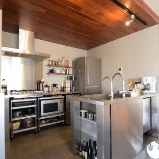 他の地域の中くらいのインダストリアルスタイルのおしゃれなキッチン (一体型シンク、オープンシェルフ、ステンレスキャビネット、ステンレスカウンター、グレーの床) の写真
