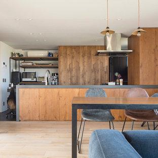 札幌のコンテンポラリースタイルのおしゃれなキッチン (フラットパネル扉のキャビネット、中間色木目調キャビネット、黒い調理設備、淡色無垢フローリング、ベージュの床、グレーのキッチンカウンター) の写真