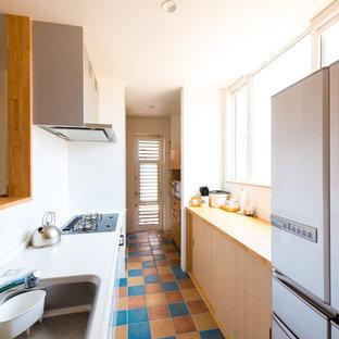 他の地域の地中海スタイルのおしゃれなキッチン (シングルシンク、フラットパネル扉のキャビネット、白いキャビネット、白いキッチンパネル、セラミックタイルの床、マルチカラーの床、茶色いキッチンカウンター) の写真