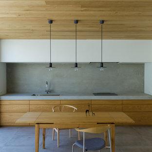 他の地域のモダンスタイルのおしゃれなキッチン (アンダーカウンターシンク、フラットパネル扉のキャビネット、中間色木目調キャビネット、コンクリートカウンター、グレーのキッチンパネル、パネルと同色の調理設備、コンクリートの床、アイランドなし、グレーの床、グレーのキッチンカウンター) の写真
