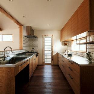 他の地域のアジアンスタイルのおしゃれなII型キッチン (一体型シンク、フラットパネル扉のキャビネット、中間色木目調キャビネット、ステンレスカウンター、白いキッチンパネル、無垢フローリング、茶色い床、グレーのキッチンカウンター) の写真