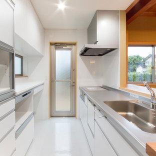 Inspiration för ett mellanstort funkis vit linjärt vitt kök och matrum, med en integrerad diskho, vita skåp, bänkskiva i rostfritt stål, vitt stänkskydd, vita vitvaror, vinylgolv, flera köksöar och vitt golv