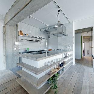 神戸のインダストリアルスタイルのおしゃれなキッチン (ドロップインシンク、ステンレスカウンター、白いキッチンパネル、サブウェイタイルのキッチンパネル、淡色無垢フローリング、ベージュの床、グレーのキッチンカウンター) の写真