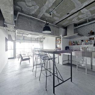 大阪の小さいインダストリアルスタイルのおしゃれなキッチン (一体型シンク、ステンレスキャビネット、ステンレスカウンター、白いキッチンパネル、サブウェイタイルのキッチンパネル、コンクリートの床、グレーの床) の写真