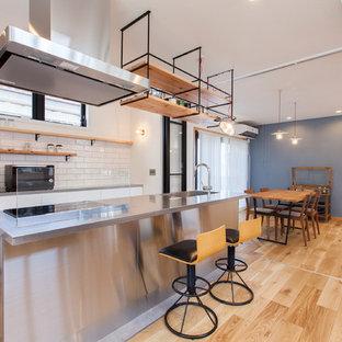他の地域のインダストリアルスタイルのおしゃれなキッチン (一体型シンク、ステンレスカウンター、白いキッチンパネル、サブウェイタイルのキッチンパネル、淡色無垢フローリング) の写真