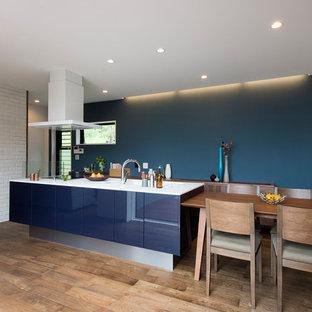 他の地域のミッドセンチュリースタイルのキッチンの画像 (フラットパネル扉のキャビネット、青いキャビネット、無垢フローリング、アイランド1つ、茶色い床)