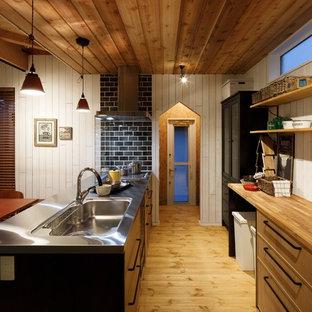 他の地域の北欧スタイルのおしゃれなキッチン (シングルシンク、フラットパネル扉のキャビネット、中間色木目調キャビネット、ステンレスカウンター、白いキッチンパネル、木材のキッチンパネル、無垢フローリング、茶色い床) の写真