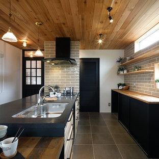 他の地域のビーチスタイルのおしゃれなキッチン (シングルシンク、落し込みパネル扉のキャビネット、白いキャビネット、ベージュキッチンパネル、グレーの床、黒いキッチンカウンター) の写真