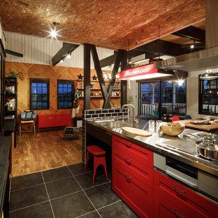 他の地域のビーチスタイルのおしゃれなキッチン (シングルシンク、落し込みパネル扉のキャビネット、赤いキャビネット、ステンレスカウンター、黒い床、黒いキッチンカウンター) の写真
