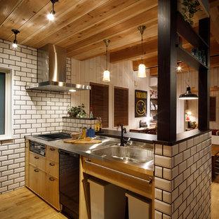 他の地域の中サイズのビーチスタイルのおしゃれなキッチン (アンダーカウンターシンク、インセット扉のキャビネット、淡色木目調キャビネット、ステンレスカウンター、白いキッチンパネル、磁器タイルのキッチンパネル、淡色無垢フローリング、茶色い床、黒いキッチンカウンター) の写真