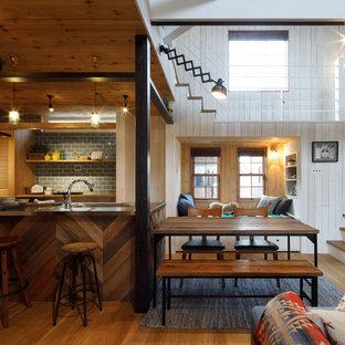 他の地域のビーチスタイルのおしゃれなキッチン (一体型シンク、ルーバー扉のキャビネット、中間色木目調キャビネット、ステンレスカウンター、青いキッチンパネル、サブウェイタイルのキッチンパネル、無垢フローリング、茶色い床、グレーのキッチンカウンター) の写真