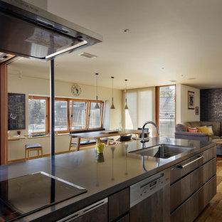 Exempel på ett stort asiatiskt svart svart kök, med en undermonterad diskho, släta luckor, skåp i slitet trä, bänkskiva i kvarts, svarta vitvaror, mellanmörkt trägolv, en köksö och brunt golv
