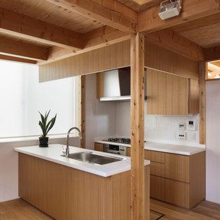 東京23区のコンテンポラリースタイルのおしゃれなキッチン (アンダーカウンターシンク、フラットパネル扉のキャビネット、中間色木目調キャビネット、白いキッチンパネル、モザイクタイルのキッチンパネル、シルバーの調理設備、無垢フローリング、茶色い床、白いキッチンカウンター) の写真