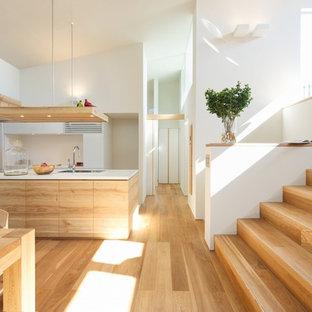 大阪の北欧スタイルのおしゃれなキッチン (フラットパネル扉のキャビネット、淡色木目調キャビネット、淡色無垢フローリング、人工大理石カウンター、白いキッチンパネル、木材のキッチンパネル、白いキッチンカウンター) の写真