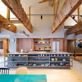 Modelo de cocina de galera, de estilo zen, abierta, con fregadero bajoencimera, armarios abiertos, suelo de madera clara, una isla, puertas de armario marrones, salpicadero verde y electrodomésticos con paneles