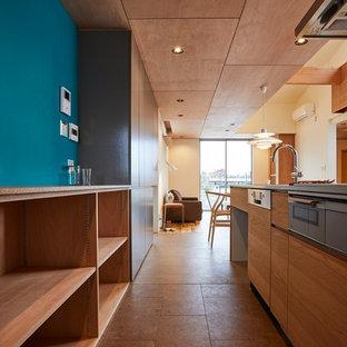 Esempio di una cucina minimalista di medie dimensioni con lavello integrato, ante lisce, ante marroni, top in acciaio inossidabile, elettrodomestici in acciaio inossidabile, pavimento in sughero, penisola, pavimento marrone, top marrone e paraspruzzi bianco