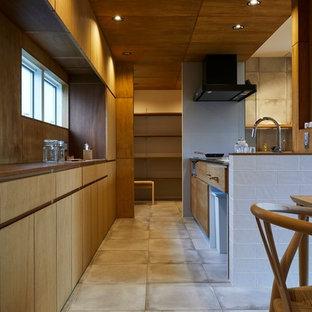 他の地域の中くらいのモダンスタイルのおしゃれなキッチン (一体型シンク、フラットパネル扉のキャビネット、茶色いキャビネット、ステンレスカウンター、メタリックのキッチンパネル、シルバーの調理設備、磁器タイルの床、グレーの床、茶色いキッチンカウンター) の写真