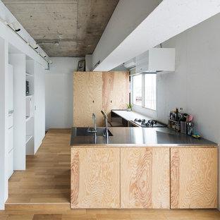 東京23区のL型モダンスタイルのダイニングキッチンの画像 (フラットパネル扉のキャビネット、白いキャビネット、ステンレスカウンター、白いキッチンパネル、無垢フローリング、ペニンシュラ型、茶色い床)