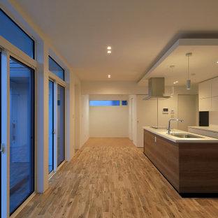 Exemple d'une cuisine ouverte linéaire moderne avec un évier intégré, un placard à porte plane, des portes de placard blanches, un plan de travail en surface solide, une crédence blanche, un électroménager encastrable, un sol en bois brun, un îlot central, un plan de travail blanc et un plafond en papier peint.