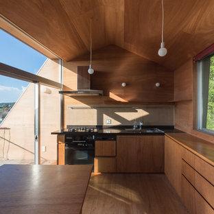 他の地域のコンテンポラリースタイルのおしゃれなキッチン (アンダーカウンターシンク、中間色木目調キャビネット、人工大理石カウンター、茶色いキッチンパネル、モザイクタイルのキッチンパネル、黒い調理設備、茶色い床、茶色いキッチンカウンター、フラットパネル扉のキャビネット、無垢フローリング) の写真