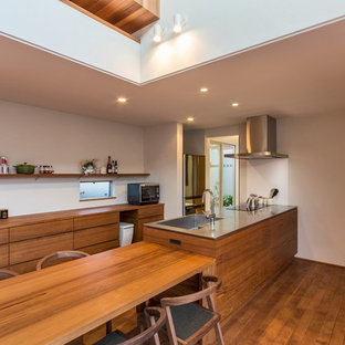 Inspiration for a modern galley eat-in kitchen in Nagoya with an integrated sink, flat-panel cabinets, medium wood cabinets, stainless steel benchtops, white splashback, stainless steel appliances, medium hardwood floors and a peninsula.