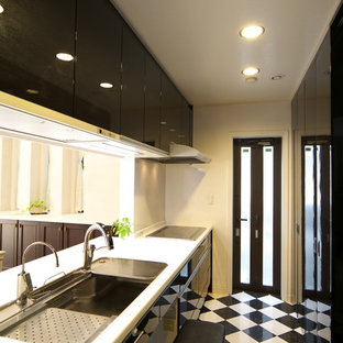 他の地域のI型モダンスタイルのキッチンの画像 (シングルシンク、フラットパネル扉のキャビネット、黒いキャビネット、ペニンシュラ型、マルチカラーの床、白いキッチンカウンター)
