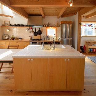 横浜のコンテンポラリースタイルのおしゃれなキッチン (一体型シンク、フラットパネル扉のキャビネット、中間色木目調キャビネット、木材カウンター、白いキッチンパネル、無垢フローリング、茶色い床) の写真
