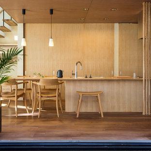 他の地域のモダンスタイルのおしゃれなキッチン (シングルシンク、フラットパネル扉のキャビネット、中間色木目調キャビネット、木材カウンター、無垢フローリング、茶色い床) の写真