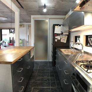 他の地域のインダストリアルスタイルのおしゃれなキッチン (一体型シンク、フラットパネル扉のキャビネット、ステンレスキャビネット、ステンレスカウンター、黒い床、茶色いキッチンカウンター) の写真