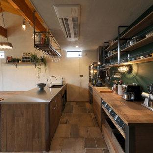 他の地域のインダストリアルスタイルのおしゃれなペニンシュラキッチン (ダブルシンク、オープンシェルフ、木材カウンター、緑のキッチンパネル、マルチカラーの床、茶色いキッチンカウンター、表し梁) の写真