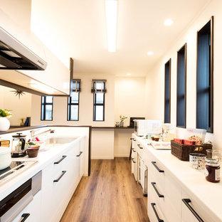 他の地域, のコンテンポラリースタイルのおしゃれなキッチン (シングルシンク、フラットパネル扉のキャビネット、白いキャビネット、白いキッチンパネル、無垢フローリング、茶色い床) の写真