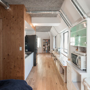 This is an example of a small industrial single-wall open plan kitchen in Tokyo with an integrated sink, flat-panel cabinets, white cabinets, stainless steel benchtops, white splashback, slate splashback, white appliances, plywood floors, no island and brown floor.