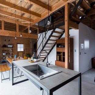 Inspiration för mellanstora industriella linjära grått kök med öppen planlösning, med betonggolv, en integrerad diskho, öppna hyllor, skåp i rostfritt stål, bänkskiva i betong, vitt stänkskydd, stänkskydd i tegel, svarta vitvaror, en köksö och grått golv
