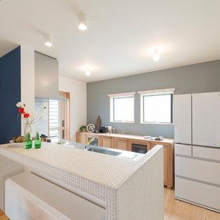 他の地域の北欧スタイルのキッチンの画像 (シングルシンク、ステンレスカウンター、淡色無垢フローリング、アイランド1つ、茶色い床)
