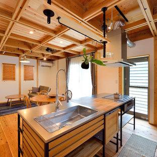 他の地域のトラディショナルスタイルのおしゃれなキッチン (シングルシンク、ステンレスカウンター、無垢フローリング、茶色い床) の写真