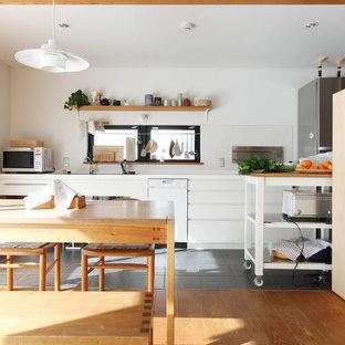 東京都下のアジアンスタイルのおしゃれなキッチン (アンダーカウンターシンク、フラットパネル扉のキャビネット、白いキャビネット、白いキッチンパネル、シルバーの調理設備の、無垢フローリング、茶色い床、白いキッチンカウンター) の写真